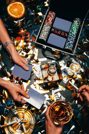 partial view of women playing poker at table with whiskey, alcoholic cocktail and cigarettes and golden confetti