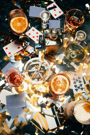 top view of cigarettes, alcoholic cocktails, playing cards, rolled banknote, credit cards and cocaine on table covered by golden confetti