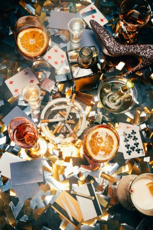 elevated view of alcoholic cocktails, playing cards, cigarettes, rolled banknote, credit cards and cocaine on table covered by golden confetti