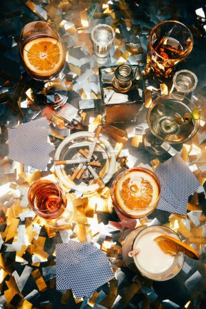 flat lay with cigarettes, alcoholic cocktails, whiskey and playing cards on table covered by golden confetti