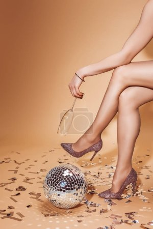 cropped image of woman sitting with empty glass near disco ball on confetti at party on beige