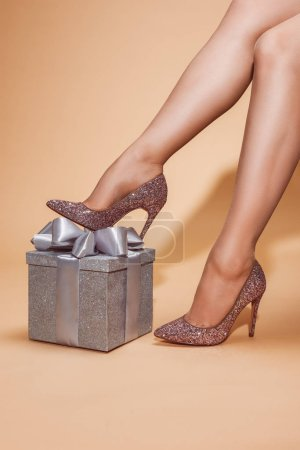 Photo for Cropped image of woman in high heels sitting near silver gift box at party on beige - Royalty Free Image