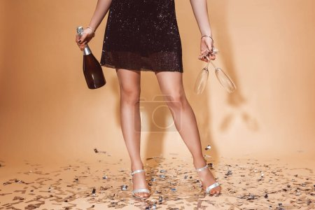 cropped image of woman holding glasses and bottle of champagne at party on beige
