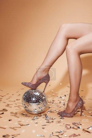 Photo pour Image recadrée de femme en talons hauts mettant jambe sur boule disco, sol beige avec confettis - image libre de droit