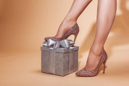 cropped image of woman putting leg on silver gift box at party on beige