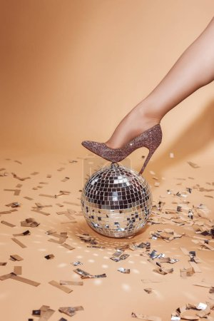 cropped image of woman putting leg on silver disco ball, confetti on floor