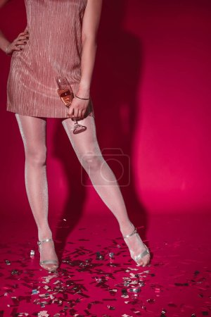 Photo for Cropped image of woman in dress standing on confetti and holding glass of champagne on burgundy - Royalty Free Image