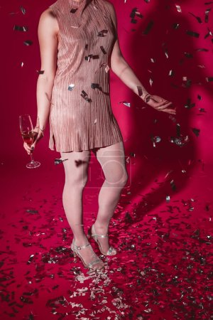 cropped image of woman in dress standing with glass of champagne under falling confetti at party on burgundy