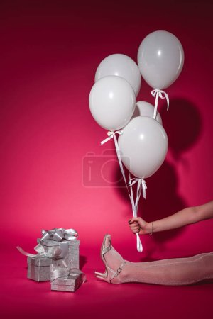 cropped image of girl sitting and holding bundle of white balloons with helium on burgundy
