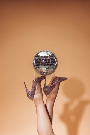 cropped image of woman holding shiny disco ball on high heels at party on beige