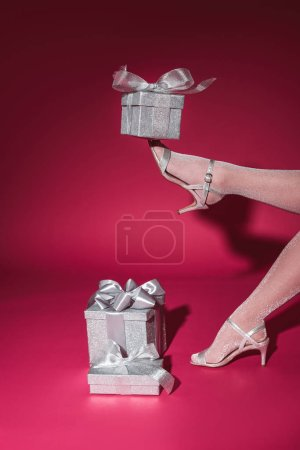 cropped image of girl holding silver gift on leg at party on burgundy