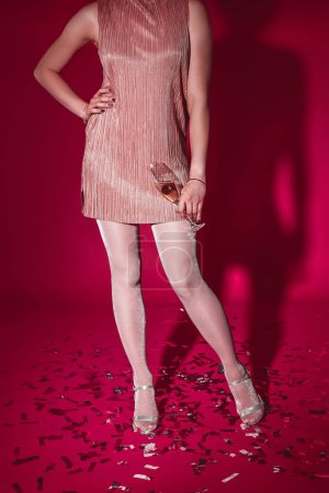 cropped image of woman in dress posing with glass of champagne on confetti at party