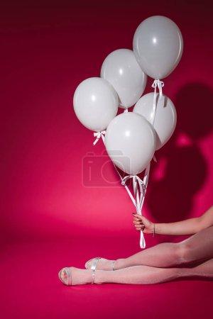 Foto de Imagen recortada de niña sentada y que paquete de globos blancos en el partido en Borgoña - Imagen libre de derechos
