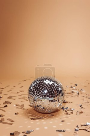 shiny silver disco ball and confetti on beige