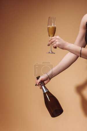 cropped image of woman holding glass and bottle of champagne at party on beige