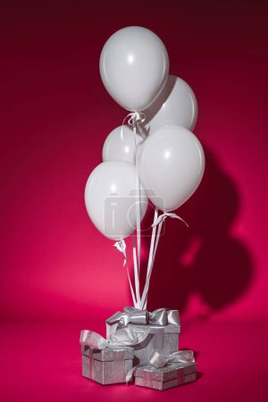 Photo for Bundle of white balloons and silver gift boxes on burgundy - Royalty Free Image