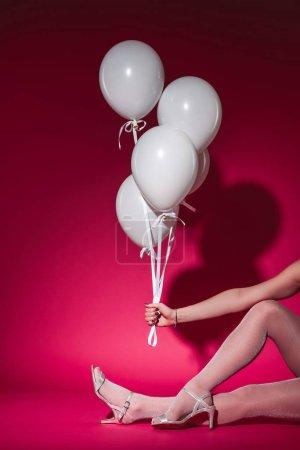 Foto de Imagen recortada de la mujer sentada y que paquete de globos blancos en el partido en Borgoña - Imagen libre de derechos