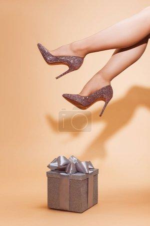 Foto de Recortar imagen de la mujer sentada encima de la caja de regalo plata en beige - Imagen libre de derechos