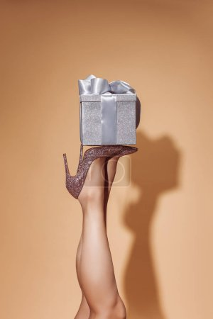 cropped image of woman holding gift box on legs at party on beige