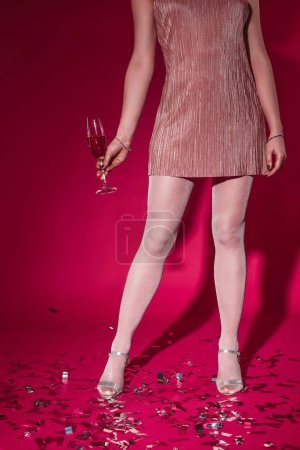 low section of woman in dress standing on confetti with glass of champagne at party on burgundy