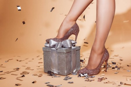 cropped image of woman putting leg on present, falling confetti on beige