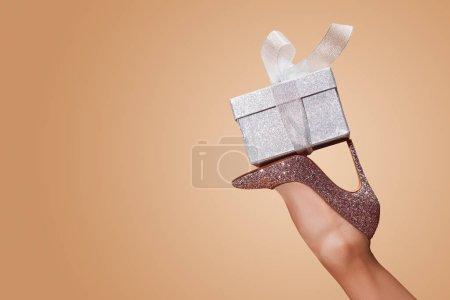 image recadrée de femme tenant la boîte-cadeau sur jambe isolée sur beige