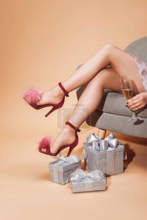 Foto de Imagen recortada de la mujer sentada en el sillón y sosteniendo la Copa de champán en fiesta en beige - Imagen libre de derechos