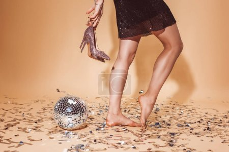 cropped image of woman holding high heels and standing on confetti at party on beige