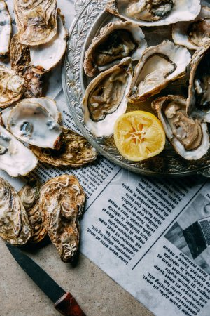 flat lay with oysters, lemon and knife on newspaper on grey surface