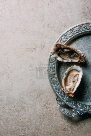 top view of oysters on metal tray on grey tabletop