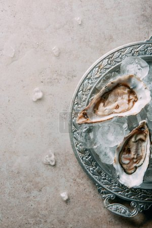 top view of oysters with ice on metal tray on grey tabletop