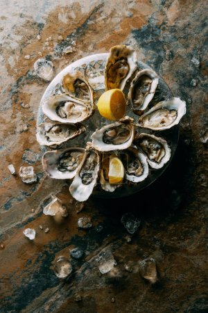 top view of oysters, ice and lemon on grungy tabletop