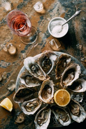 flat lay with glass of wine, oysters with ice and lemon pieces on grungy tabletop