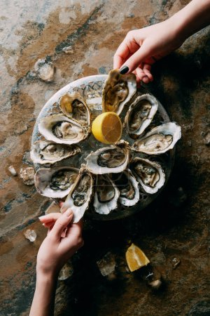 Photo for Partial view of women at grungy tabletop with oysters, ice and lemon - Royalty Free Image