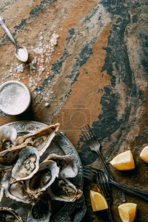 top view of arrangement of oysters and lemon pieces on grungy tabletop