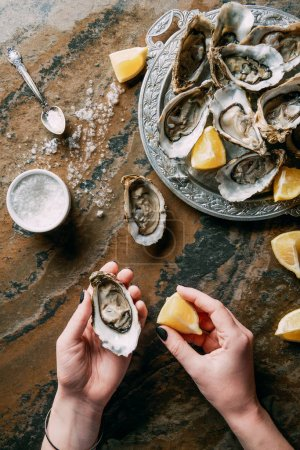 Photo for Cropped shot of woman holding oyster and lemon piece in hand at grungy tabletop - Royalty Free Image