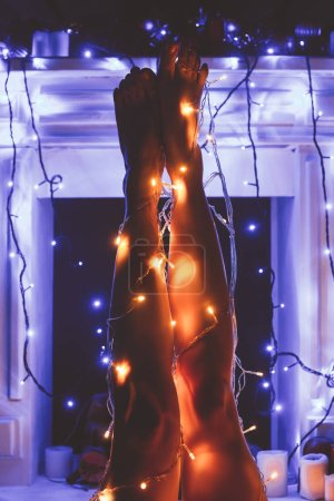 partial view of woman with christmas festive lights around
