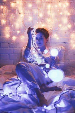 beautiful woman in pajamas with festive lights sitting on bed at home