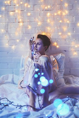 pensive woman in pajamas with christmas lights resting on bed at home