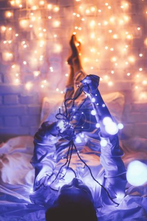 woman in pajamas resting on bed with christmas lights around