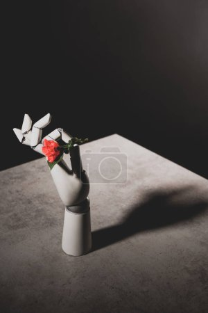 Photo for Pink rose flower in robotic hand on stone table on black background - Royalty Free Image