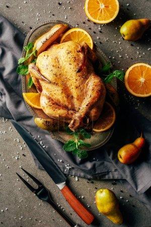 Photo pour Vue de dessus du poulet frit aux oranges, poires et verdure sur plateau - image libre de droit