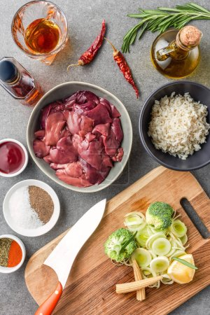 Photo for Top view of raw meat, rice, spices, oil, cognac, peppers and broccoli with onion on cutting board - Royalty Free Image