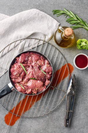 Photo for Raw meat in fried pan on metal grille with oil, broccoli and sauce - Royalty Free Image