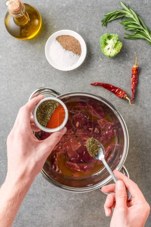 Photo for Cropped view of woman adding spices in raw meat in pot with oil, peppers, broccoli and rosemary - Royalty Free Image