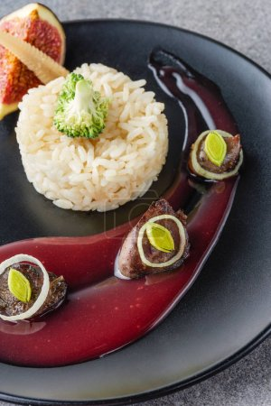 Photo for Close up of rice, broccoli, fig and fried meat with sauce on black plate - Royalty Free Image