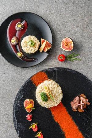Photo pour Vue de dessus de riz, de brocoli, de figue et de viande frite sauce sur plaques noires - image libre de droit