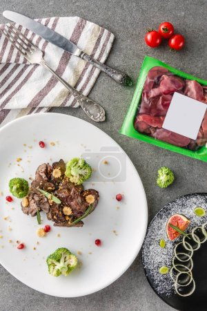 Photo for Top view of broccoli and fried meat on white plate and fig with onion on black plate with raw meat on table - Royalty Free Image