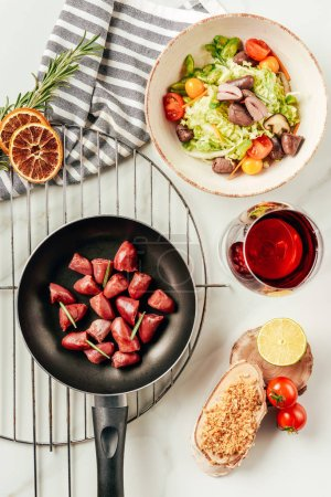 top view of meat in frying pan and salad with glass of wine