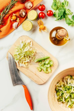 Photo for Cabbage and celery on cutting board with bottle of oil, cherry tomatoes, limes and rosemary - Royalty Free Image
